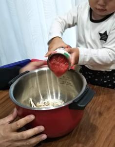 ホットクックに子供がトマト缶を投入している