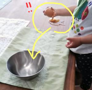 卵を割るのを失敗している2歳児
