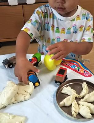 おもちゃと粘土の融合遊びをする息子