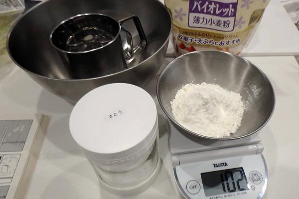 小麦粉と砂糖を量りで量っている