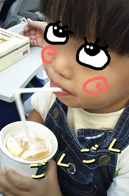 飛行機の機内でジュースを飲む子供