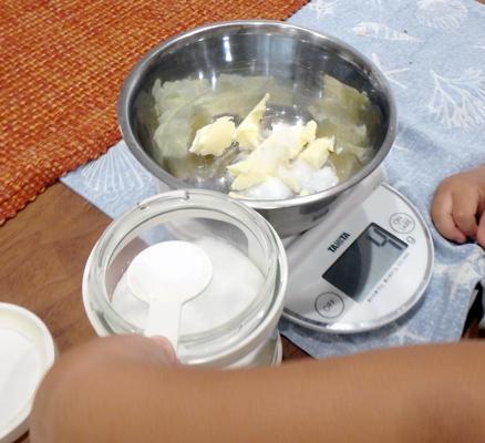 バターと砂糖を量りで量っている