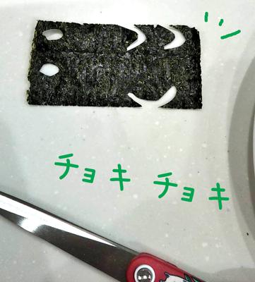 海苔をハサミで切って顔のパーツを作っている