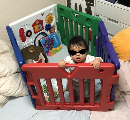 ベビーゲートに閉じ込められている赤ちゃんの写真