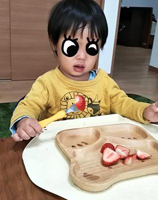 イスに座って上手に苺を食べる1歳
