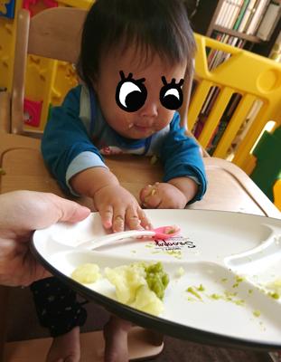 ビニール製のエプロンをつけて離乳食を食べる子ども