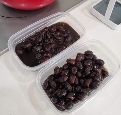 ホットクックで作った黒豆をタッパーに移している