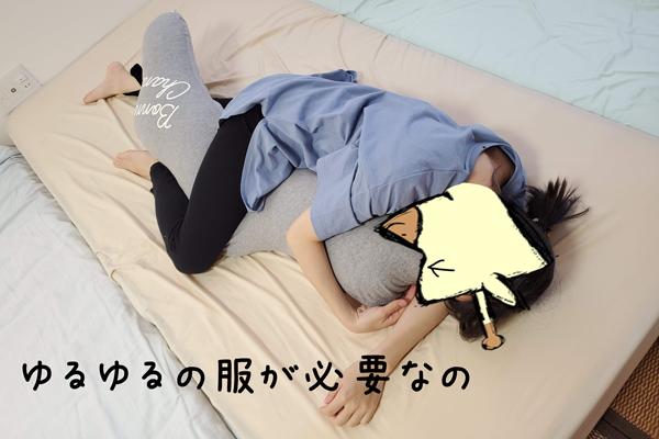 つわり中に抱き枕を抱く妊婦