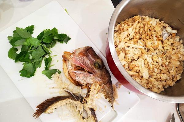 炊きあがった鯛めしからお頭と鯛を取り除いて三つ葉を用意している所